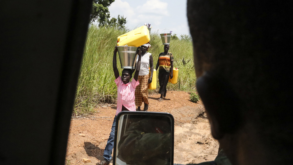 Several refugees walk along the side of the road, carrying large jugs of water on their heads.
