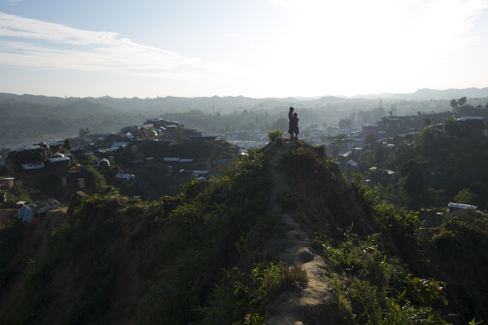 A view from afar of a hilltop with two children standing atop