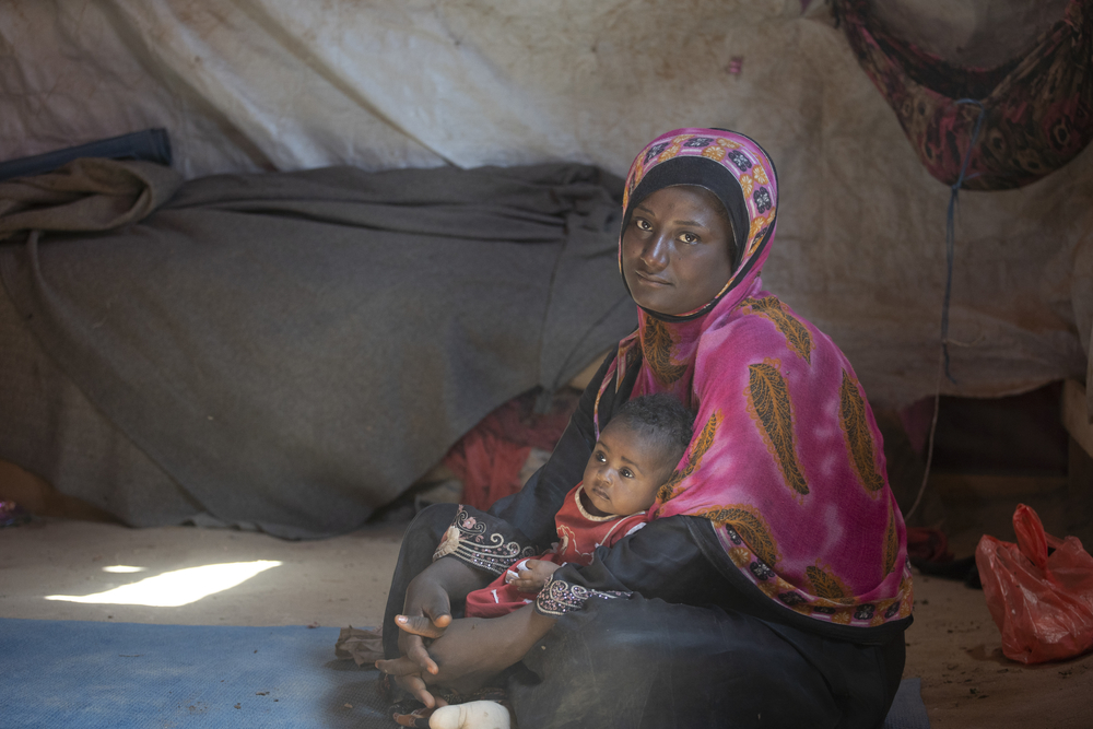 Photo of woman in Yemen with her child in a displacement camp.