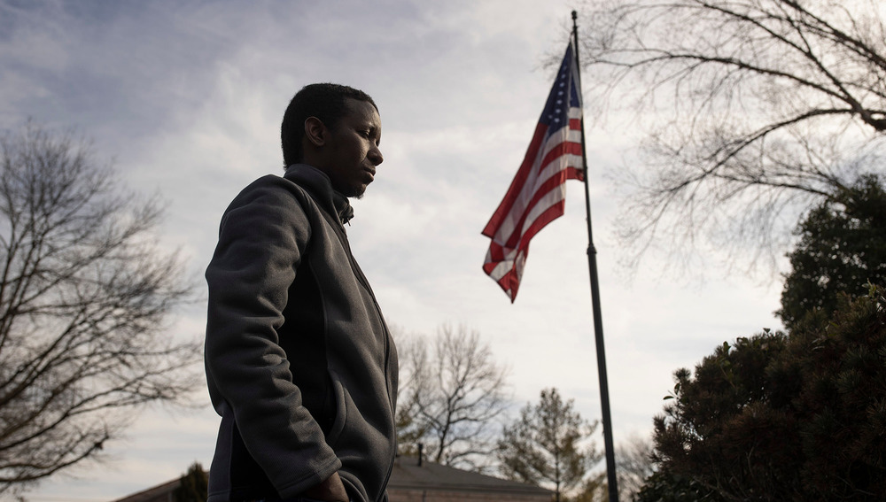 Hussein Mumin walks in front of a raised American flag.