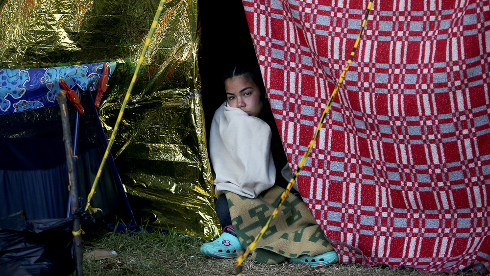 A Venezuelan migrant woman looks out the opening of a makeshift shelter at the camera.