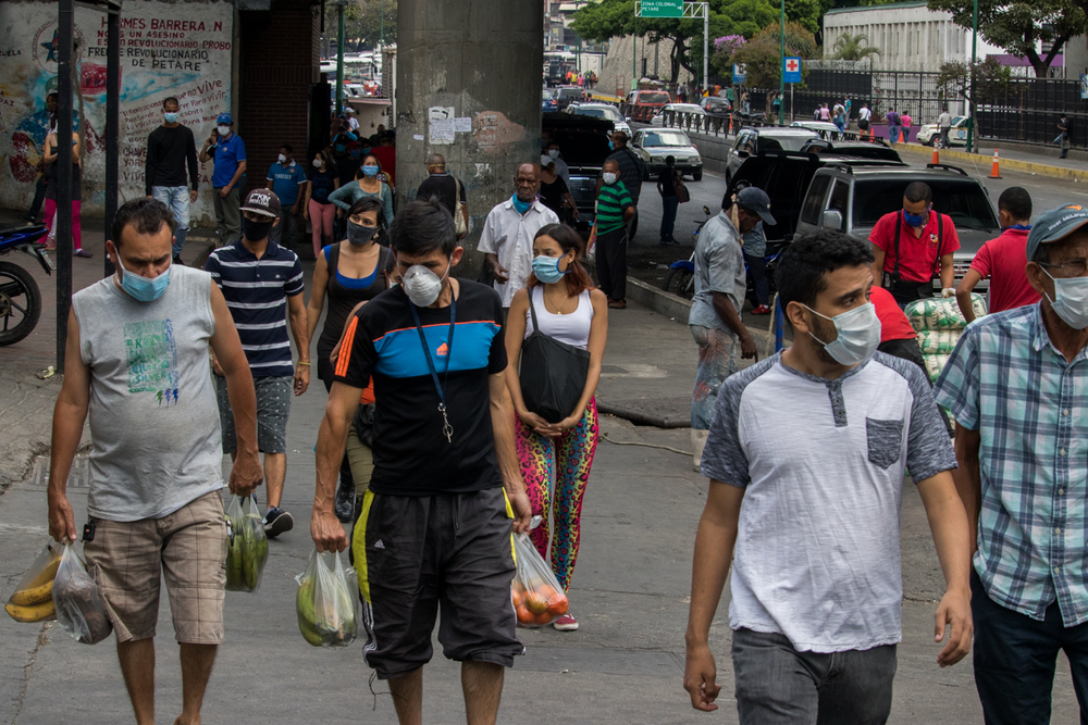 Many people, most wearing masks, crowd the streets of Petare
