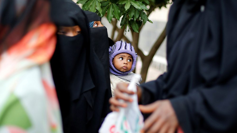 A woman from the Muhamasheen community holds her son at a charity clinic in Sanaa