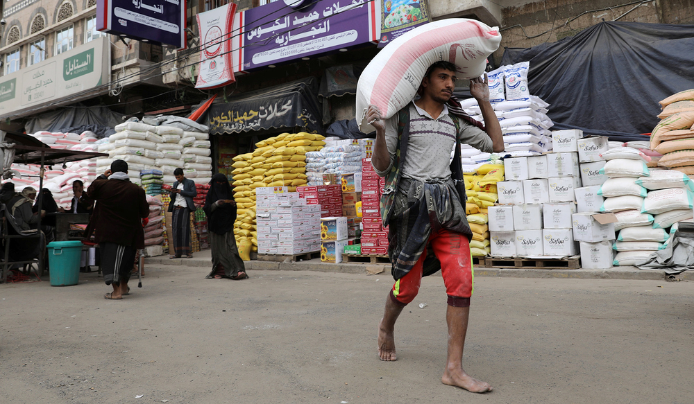 A worker carries a sack of wheat flour in Sana'a, Yemen