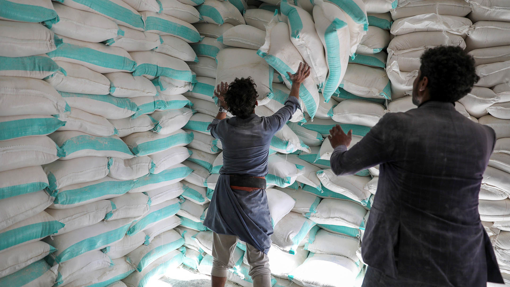 Workers handle sacks of wheat flour at a World Food Programme distribution centre in the Yemeni capital of Sana'a.