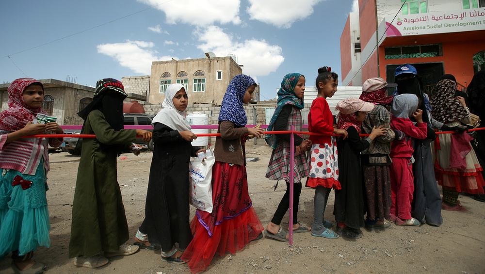 Yemeni girls queue outside a charity food distribution centre during the Muslim holy month of Ramadan in Sana'a, May 2019.