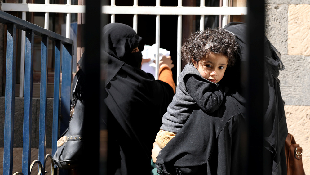 A boy being held by his mother, who is waiting for foodstuff assistance at a window counter, looks at the camera through an iron bar fence.