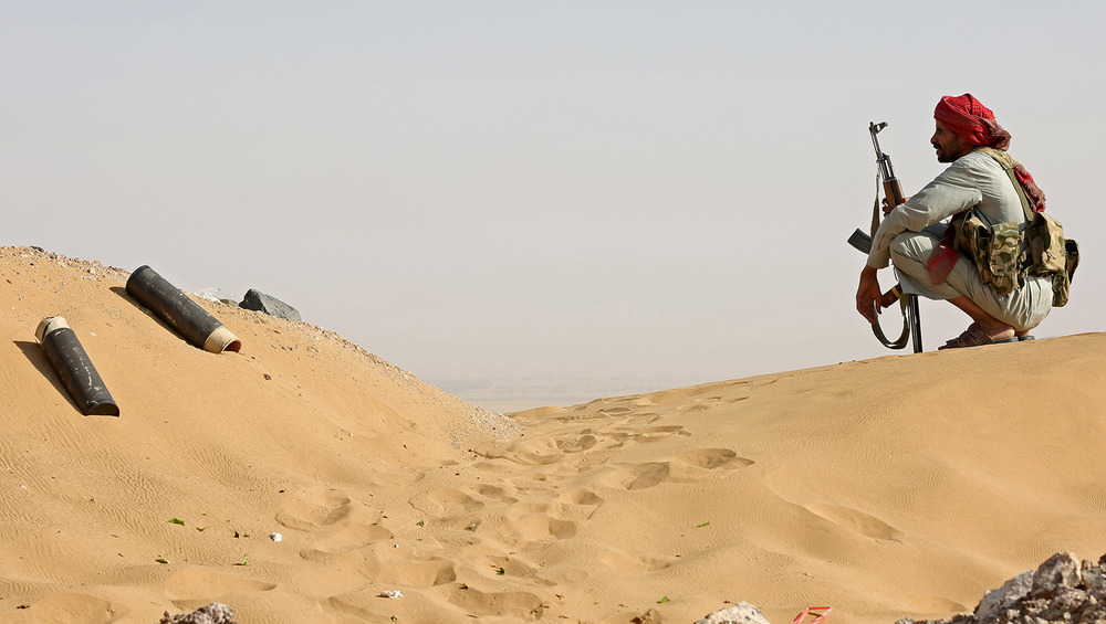 A man crouches on a sand dune, holding a rifle