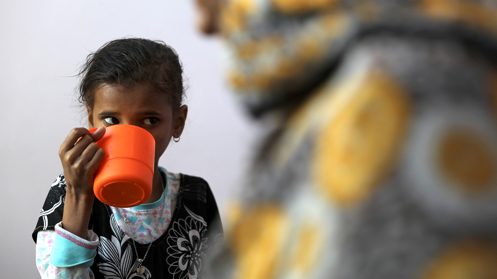 A young girl drinks out of an orange plastic cup on the left hand side of the image, while of the right hand side the blurred outline of a figure fills the foreground