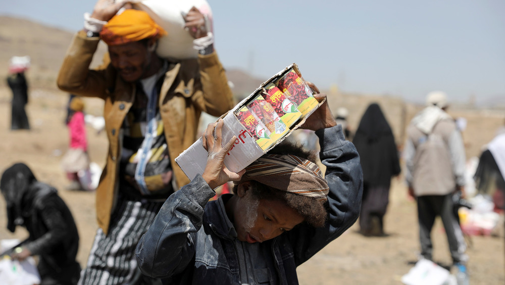 A youth and a man carry food aid on their shoulders in the sun.