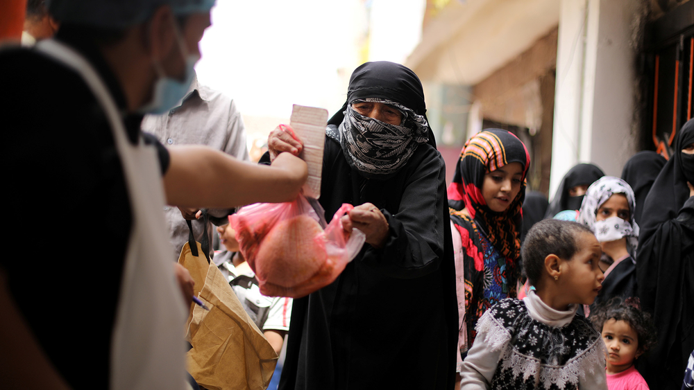 A worker hands out bread rations at a charity kitchen in Sana'a