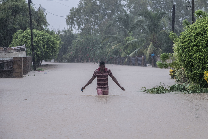 A man stands in the middle of a road with water up to his thighs