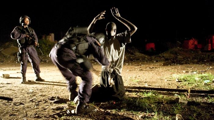 Photo: UN Photo/Christopher Herwig -Un policier libérien fouille un suspect à la recherche de drogue