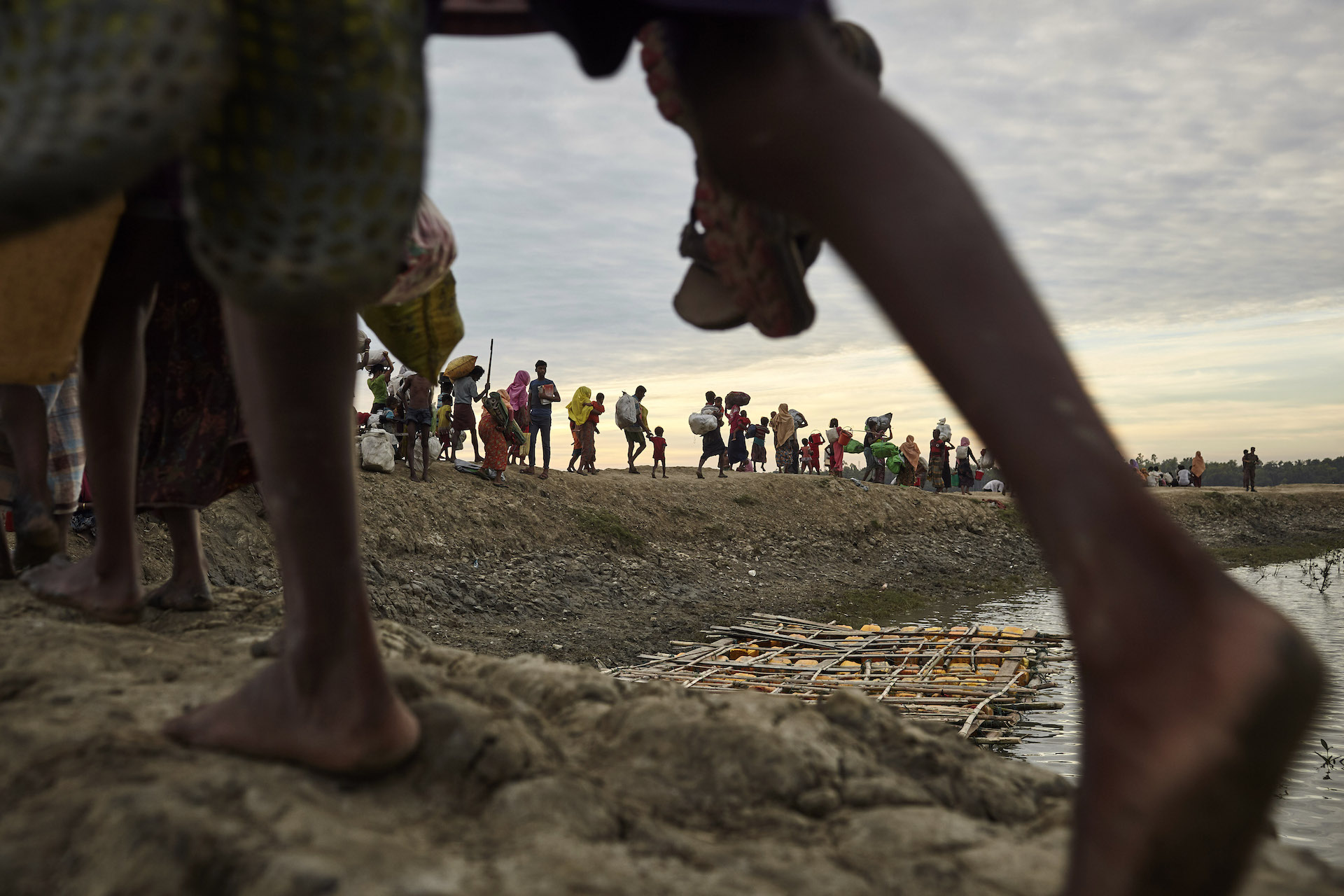 Rohingya refugees walk on an embankment of the Naf River