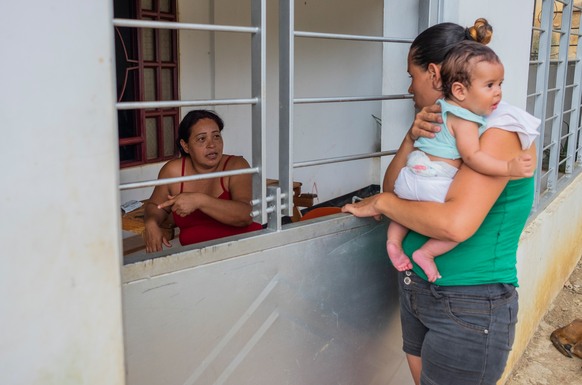 Marnellys Muentes (left) and her neighbour Élida Betancourt (right) speak through the railings of Muentes' house.