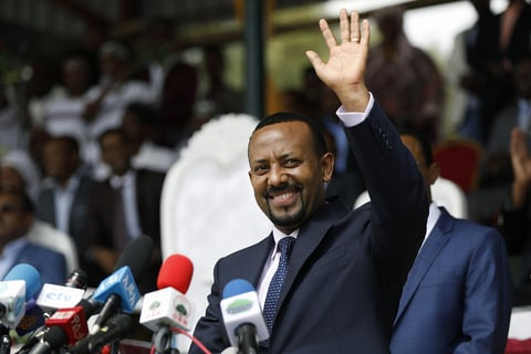 Ethiopian Prime Minister Abiy Ahmed waving in front of microphones.