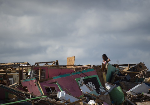 Margie Gerthadauphin looks over her destroyed home as she tries to salvage any belongings in Marsh Harbour, Bahamas, on 10 September 2019.