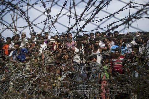 "Rohingya refugees gathering behind a barbed-wire fence in a temporary settlement setup in a ""no man's land"" border zone between Myanmar and Bangladesh"