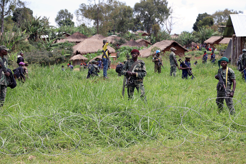 Photo of soldiers in tall grass with barbed wire in Ituri province of DRC