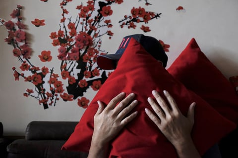 A man holds a red pillow in front of his face