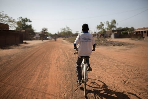 A young person rides on a bike on a dirt road away from camera
