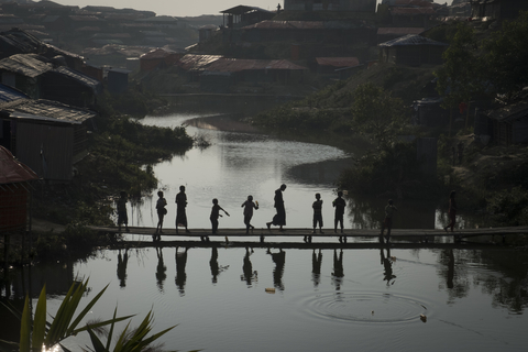 A group of Rohingya children gather on a bamboo bridge in Kutupalong makeshift settlement in Bangladesh's Cox's Bazar District on 11 January 2018
