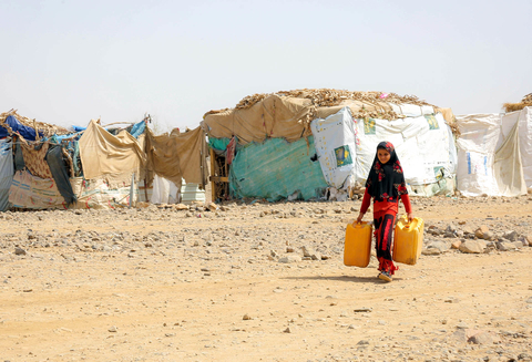 Photo of a young girl in Yemen with a watering can at a dry camp for displaced people.