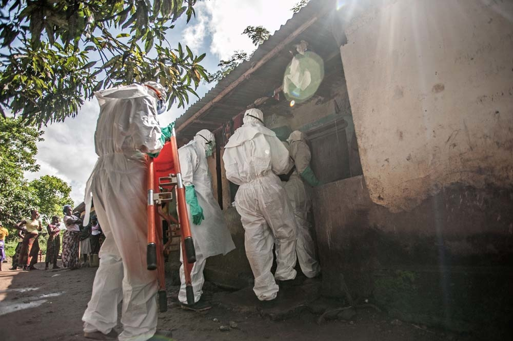 Burial workers in protective white suits enter a building