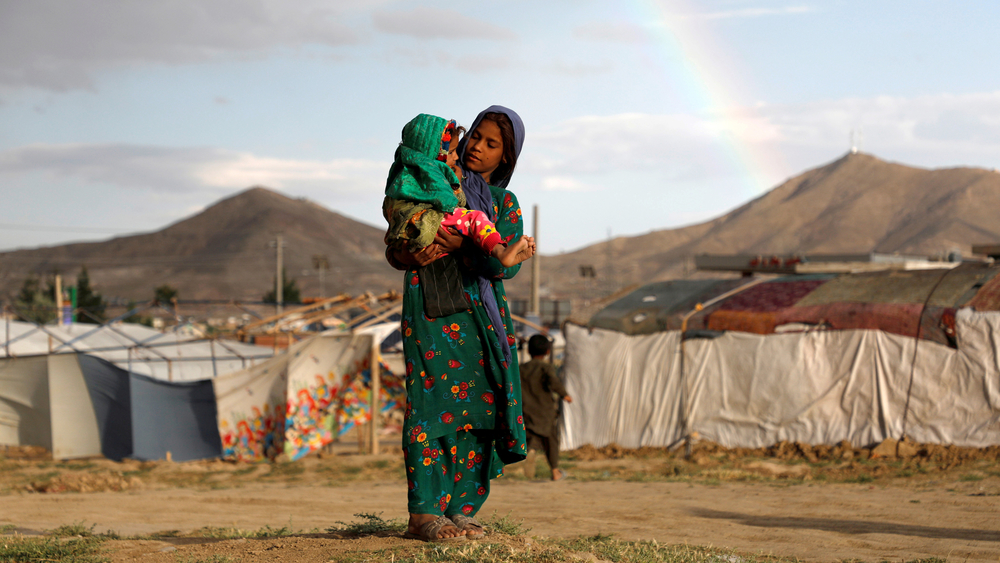 An Afghan girl carries a child near their shelter at a refugee camp on the outskirts of Kabul. Urban displacement in cities like the Afghan capital is one of our 10 crises to watch in 2020.
