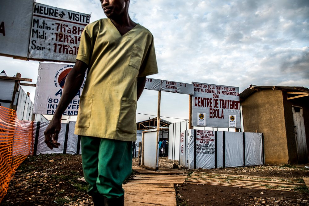 Photo of a health worker walks by the Ebola Treatment Center managed by Alima.