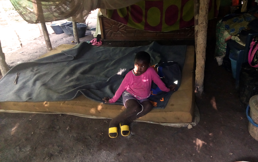 A little girl relaxes on a mattress in a tent