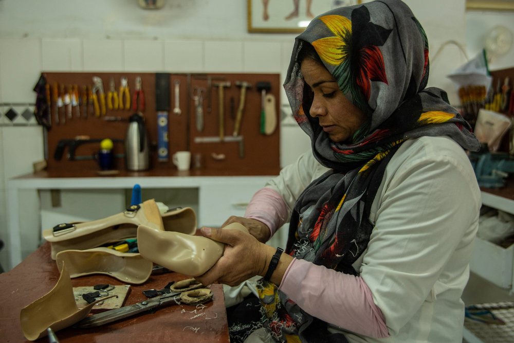 A woman works on a prosthetic limb.