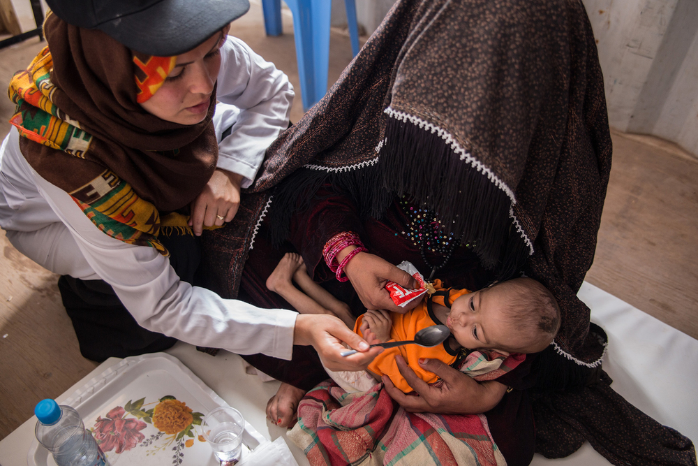 A nurse feeds a malnourished child at a mobile clinic for displaced families in western Afghanistan's Herat. Several major aid groups say it's now safer to be headquartered outside the capital, Kabul.