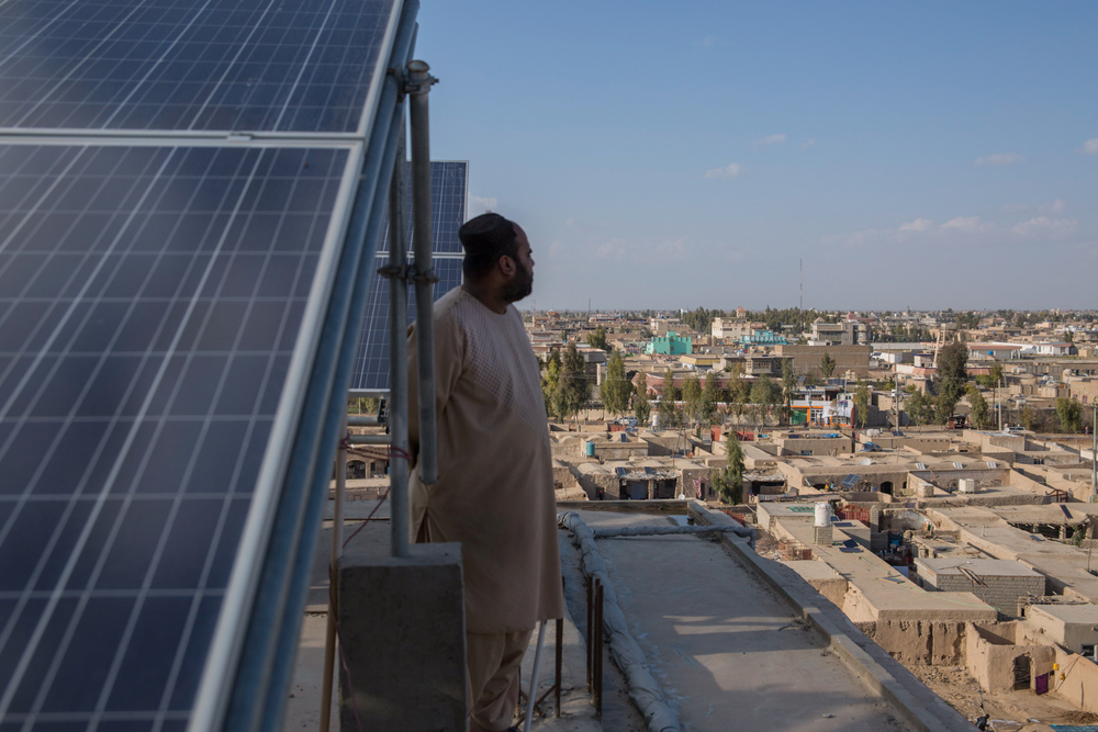 Photo of a man in Afghanistan on a roof with solar panels