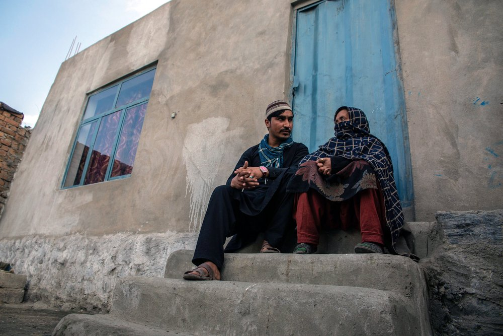 Photo of people who have returned to Afghanistan near Jalalabad sitting outside of their home.
