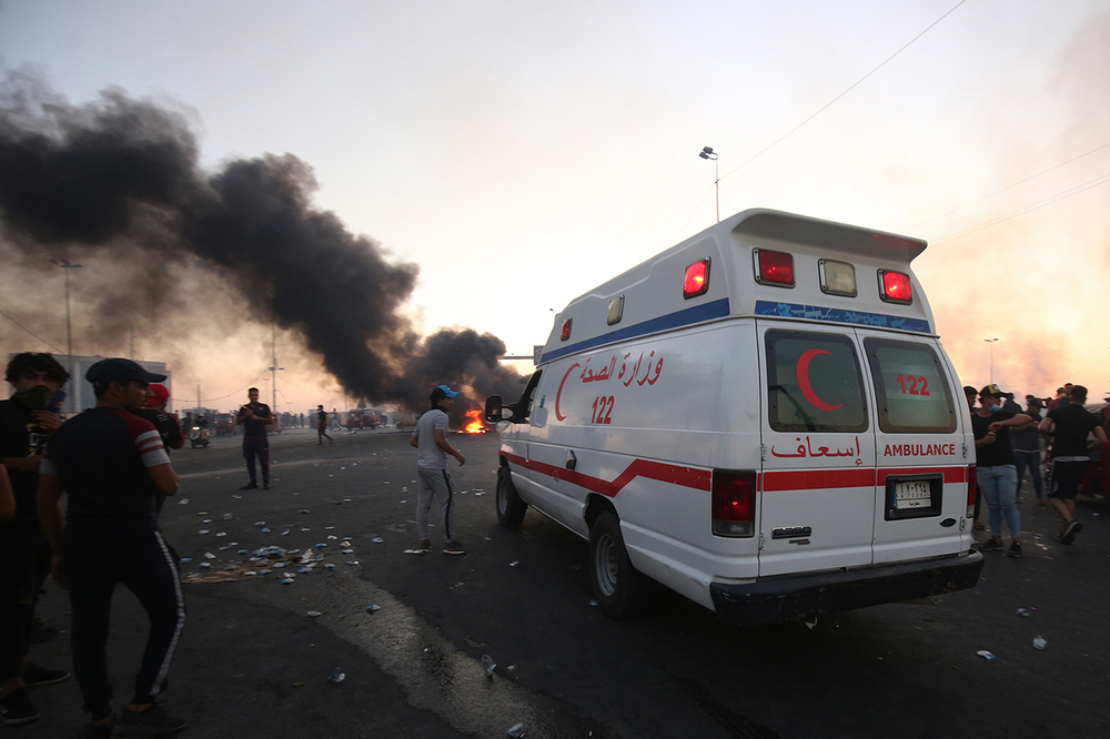 An ambulance in Baghdad protests with smoke and turmoil.