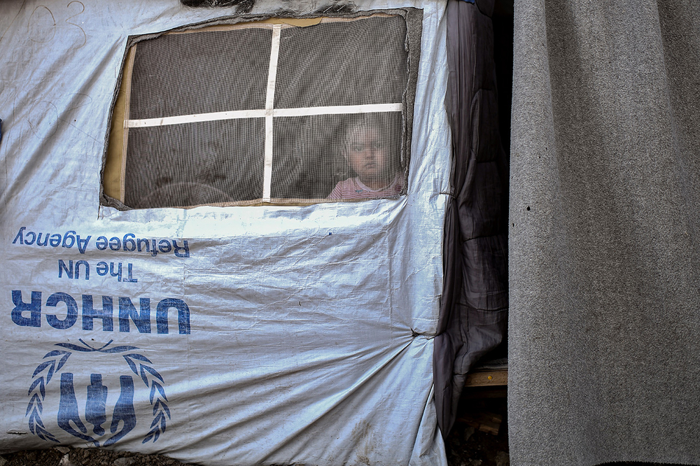 A child looks out of a tent in a camp next to the Moria detention centre on the island of Lesvos.