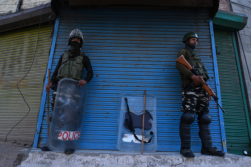 Two Indian paramilitary troopers stand guard against a closed business on a corner