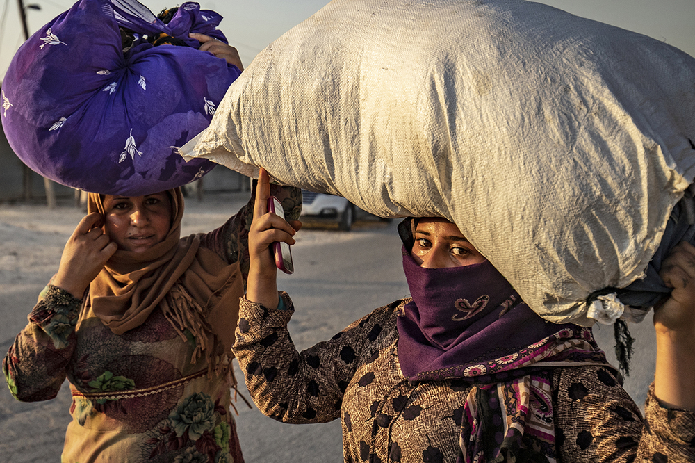 Syrian women carry their belongings over their heads as civilians flee amid Turkish bombardment of northeastern Syria.