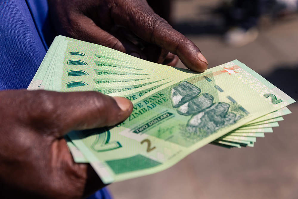 The new Zimbabwean dollar, pictured here in Harare on 12 November, may help alleviate cash flow problems but won't tackle the roots of the country's economic crisis.