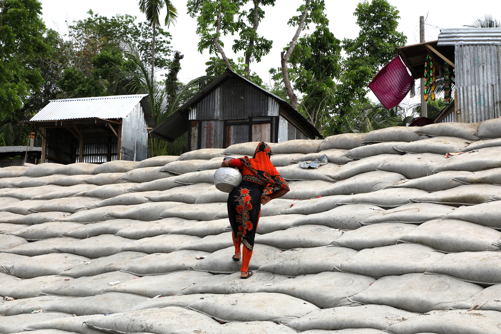 Photo of a woman in Bangladesh walking up a mountain of sand bags from the river