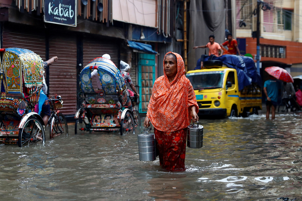 Commuters move through a water-logged street after heavy rain in Dhaka, Bangladesh, 21 July 2020.