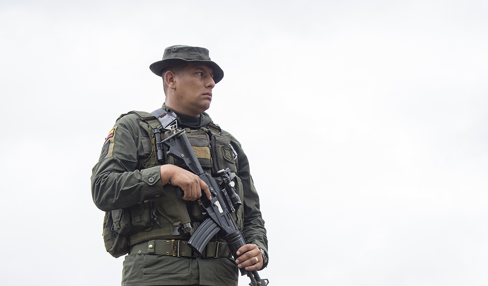 A guard in camo with a rifle against the sky