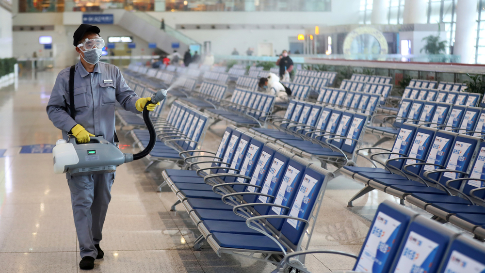 As coronavirus cases rise worldwide, a worker disinfects a waiting hall at the Nanjing Railway Station in China's Jiangsu province.