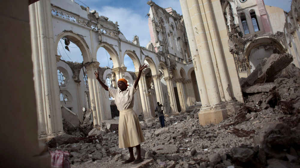 A woman prays among the rubble of the Cathedral of Our Lady of the Assumption that got destroyed in the 12 January 2010 earthquake in Port-au-Prince, Haiti.