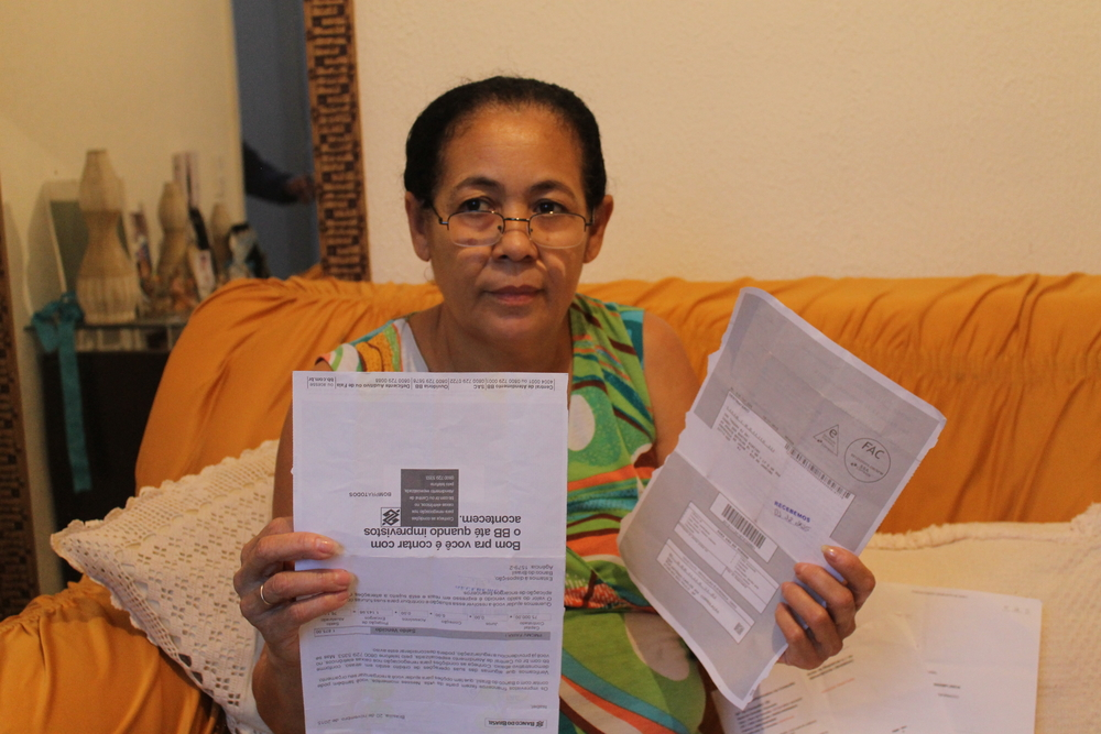 A resident of Rio de Janiero holds resettlement papers