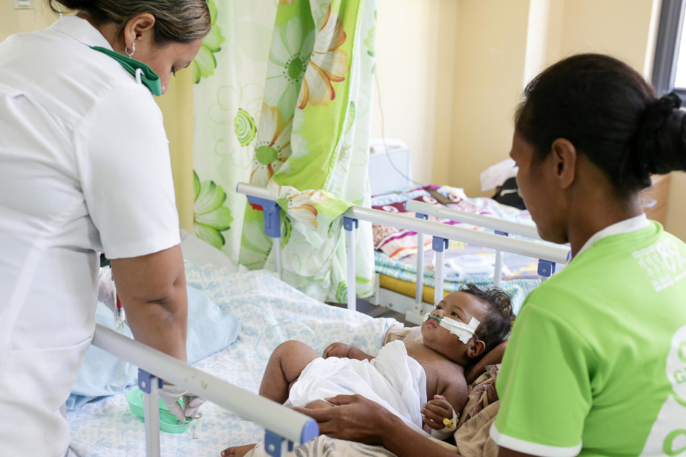 Registered Nurse Vaipou Fainu'u prepares a Vitamin A supplement for a baby in Samoa.