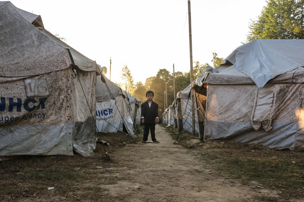 A boy stands in the middle of a displacement camp on a church compound near Myitkyina