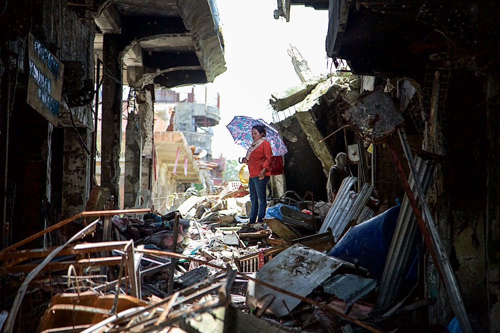 A woman with an umbrella stands on rubble as light breaks through