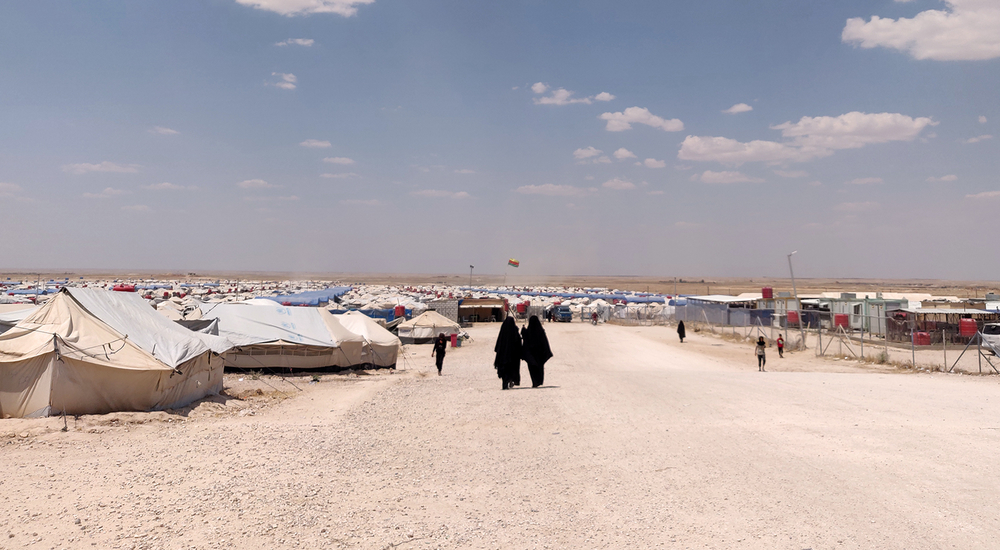 Photo of al-Hol camp in Syria showing a dry landscape and temporary shelters.